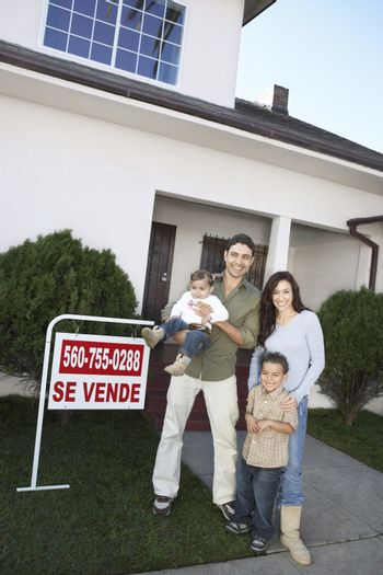 Portrait of a happy family standing in front of house for sale