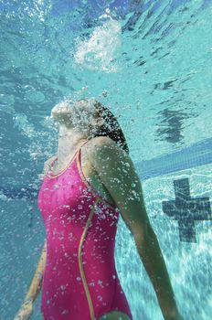 Young Caucasian female swimmer swimming underwater
