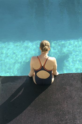 High angle view of young female swimmer sitting at the edge of the pool
