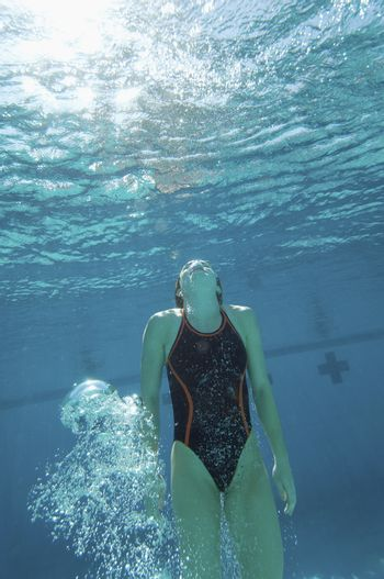 Young female swimmer holding breath under water in the pool