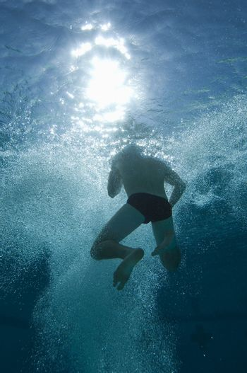 Low angle view of a male swimmer holding breath underwater