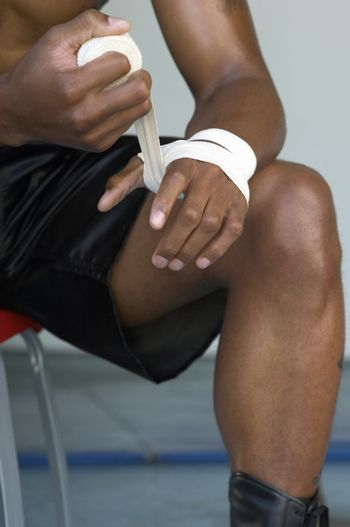 Close-up of a boxer wrapping bandage to his hand