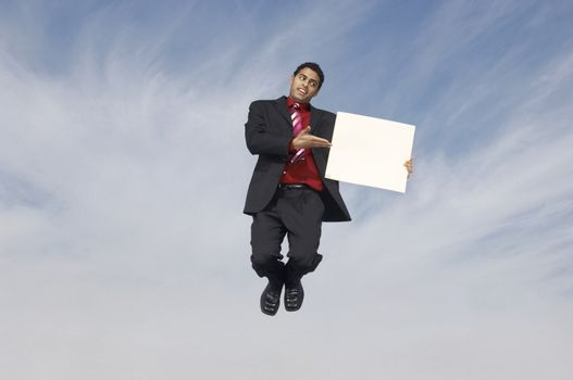 Businessman pointing while showing placard in midair