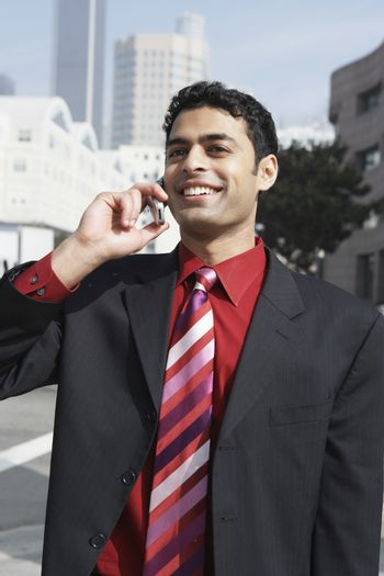 Happy mixed race businessman on a call