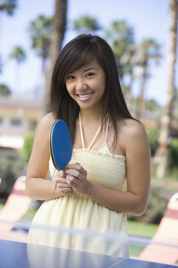 Portrait of a cheerful young woman holding a table tennis bat