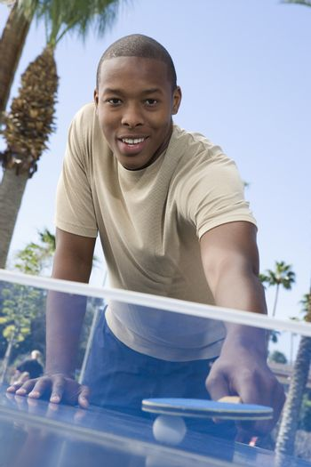 Portrait of a young African American man playing table tennis