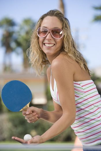 Portrait of cheerful young woman playing table tennis