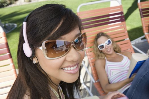 Portrait of woman listening to music with friend reading a novel in the background