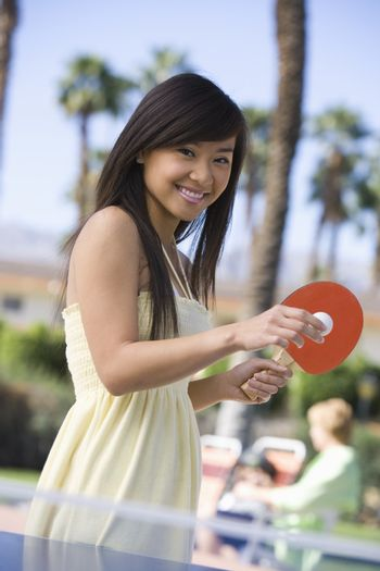 Portrait of a happy female playing table tennis with person in the background