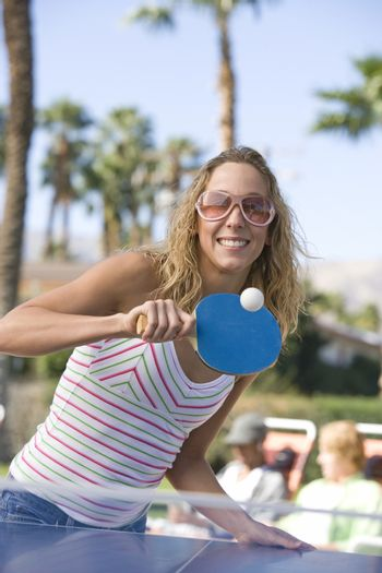 Portrait of a young female playing table tennis with people in background