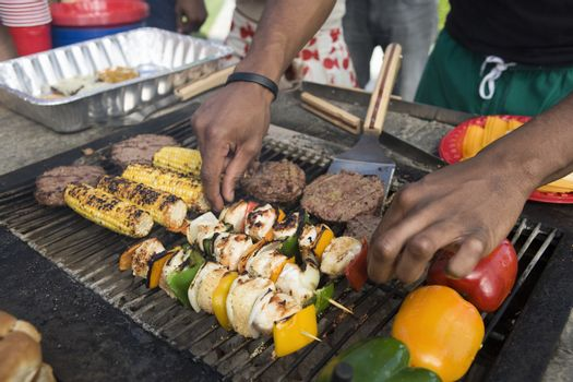 Man picking up skewers from barbecue to serve
