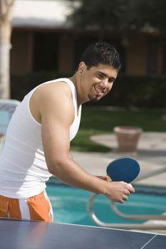 Young Hispanic Latin man playing table tennis