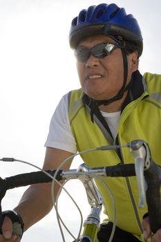 Senior man in sportswear riding bicycle