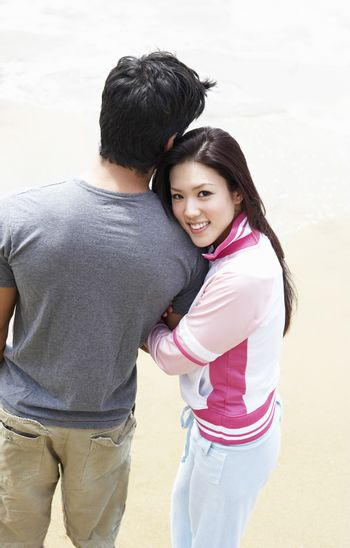 Young couple arm in arm on beach elevated view