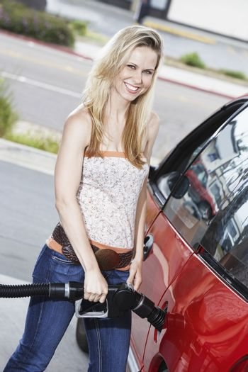 Young woman filling car with gas at gas station portrait