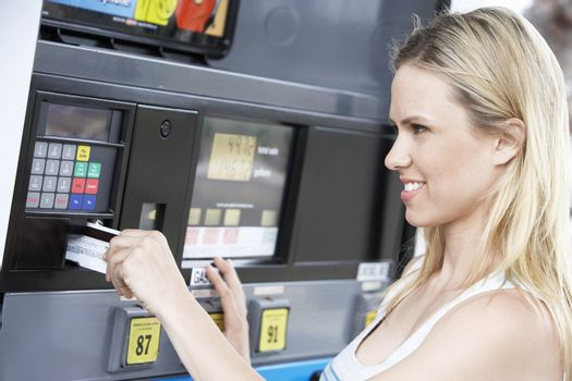 Young woman paying with credit card at gas pump head and shoulders