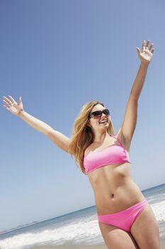 Carefree young woman in pink bikini on beach