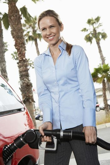 Young woman filling car at gas station