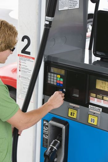 Young man using his debit card to pay for gasoline at the pump