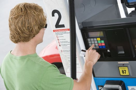 Young man using his debit card to pay for gasoline at the fuel station