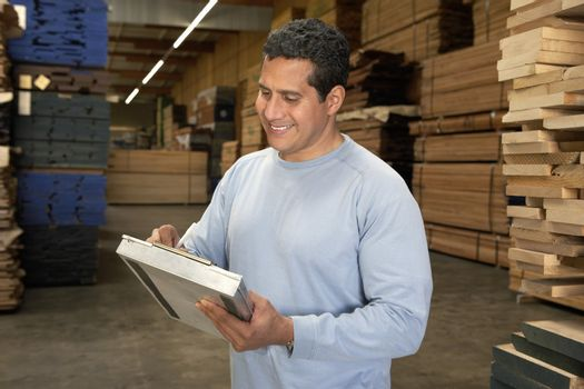 Happy middle aged man checking lumber in warehouse