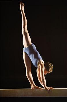 Gymnast (13-15) striking pose on balance beam