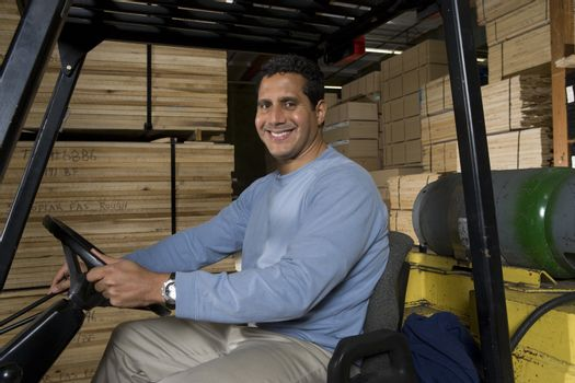 Portrait of a happy mature warehouse worker sitting in forklift at warehouse