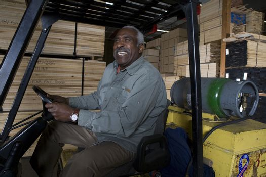 Happy senior warehouse worker sitting in forklift at warehouse
