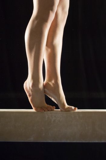Closeup low section of a female gymnast on balance beam against black background