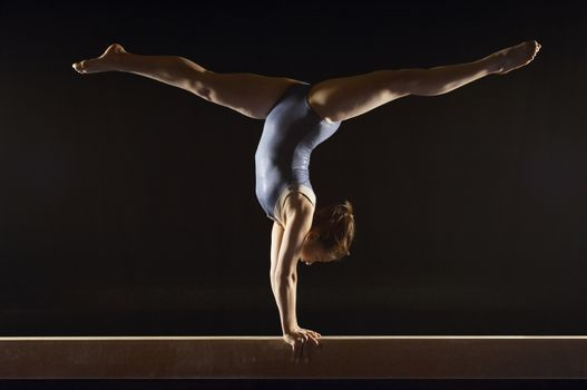 Gymnast (13-15) doing split handstand on balance beam side view