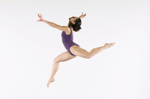Gymnast (13-15) leaping in air side view
