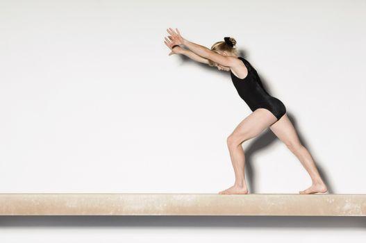 Gymnast(13-15)  on balance beam preparing to do handstand side view