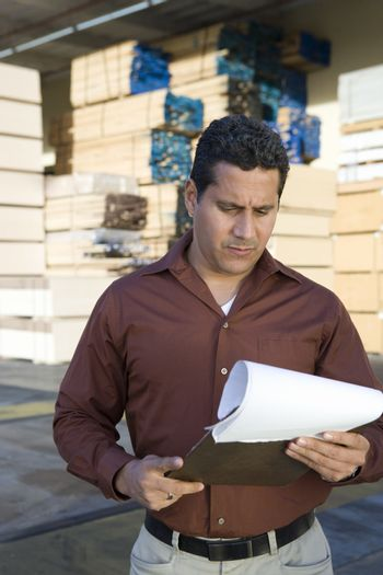 Mature male warehouse worker checking his reports