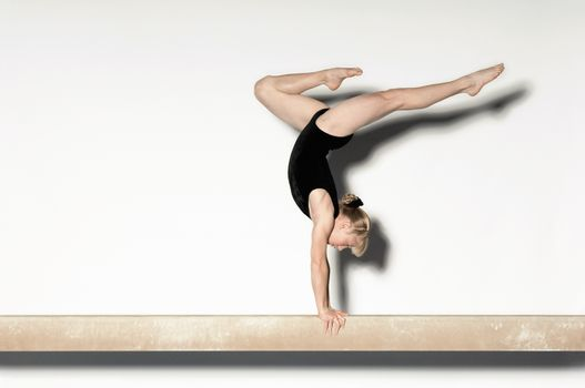 Gymnast (13-15) doing handstand on balance beam side view