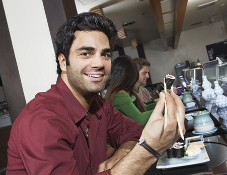 Man Having Sushi With Chopsticks