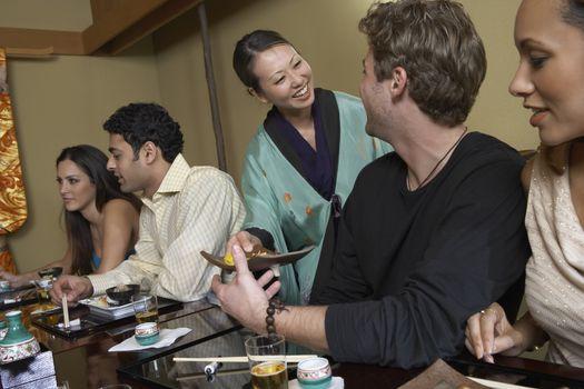 Waitress serving sushi to restaurant