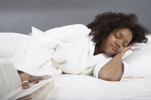 Young African American woman sleeping while holding novel