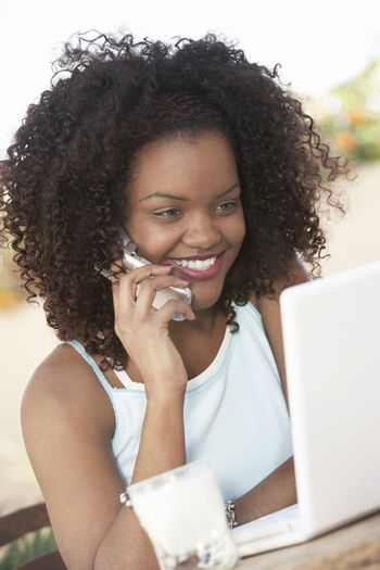 Woman With Laptop Using Cell Phone