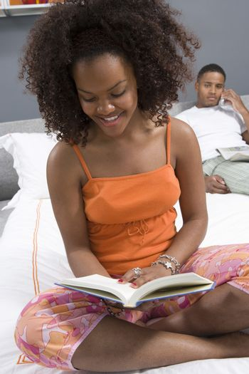 Happy young woman reading novel with man on call in bedroom