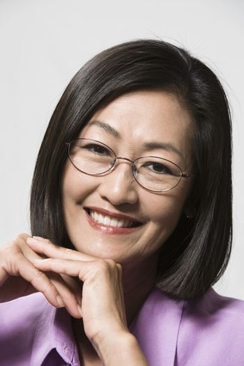 Close-up portrait of a happy Chinese woman with hands on chin isolated over white background