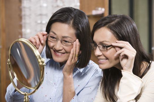 Happy women trying out spectacles in the shop