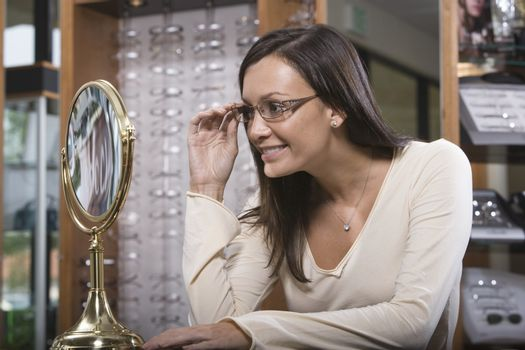 Hispanic woman trying on spectacles at shop
