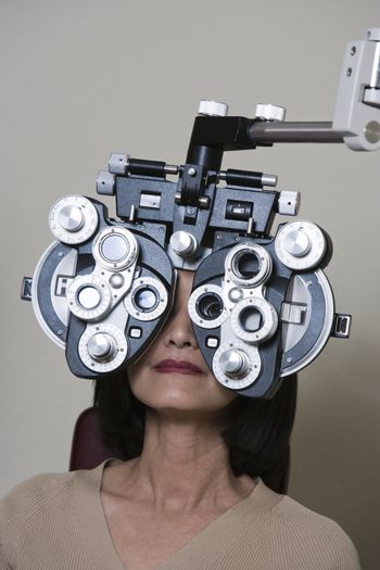 Woman having her vision checked with a Phoropter over grey background