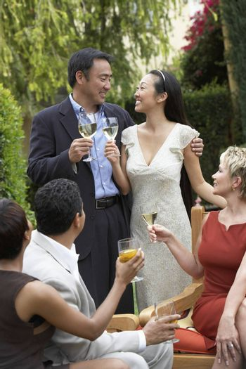 Friends toasting with drinks in garden