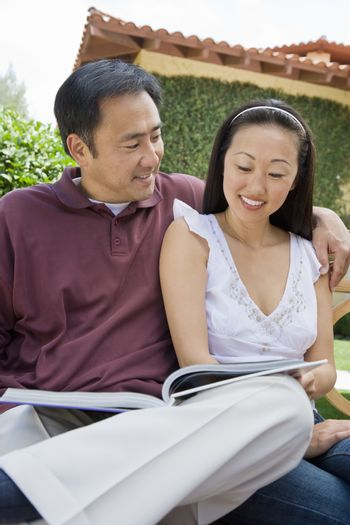 Happy mature couple with arm around reading novel outdoors