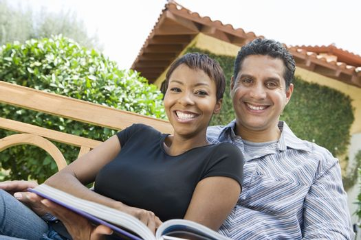 Portrait of happy relaxed couple with novel