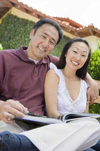 Portrait of happy mature couple with arm around reading novel outdoors