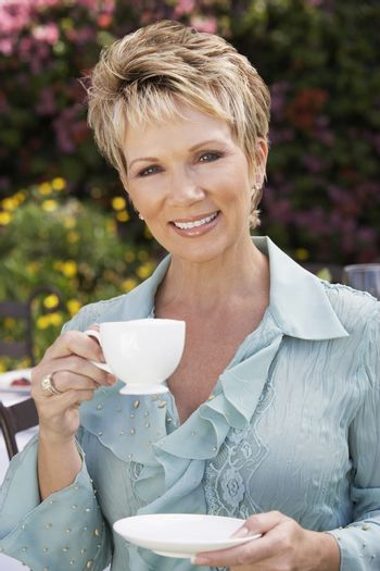 Portrait of a happy mature woman holding cup and saucer