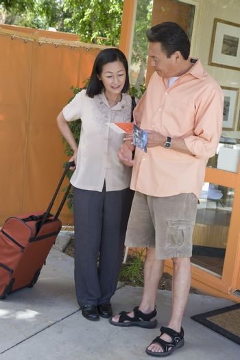 Full length of a couple looking at pamphlet on vacation