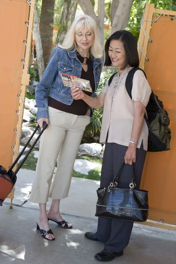 Full length of happy female friends reading pamphlet at the entrance of resort